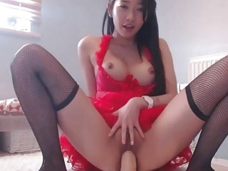 Amateur Asian in fishnet stockings rides a dildo