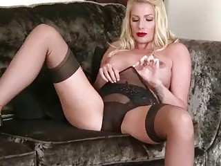 Busty blonde is masturbating on the couch
