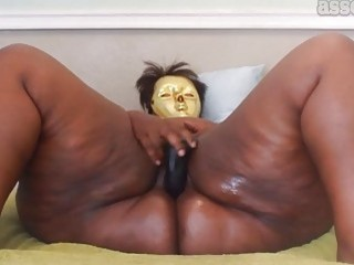 Ebony fatty with a mask playing with her toy